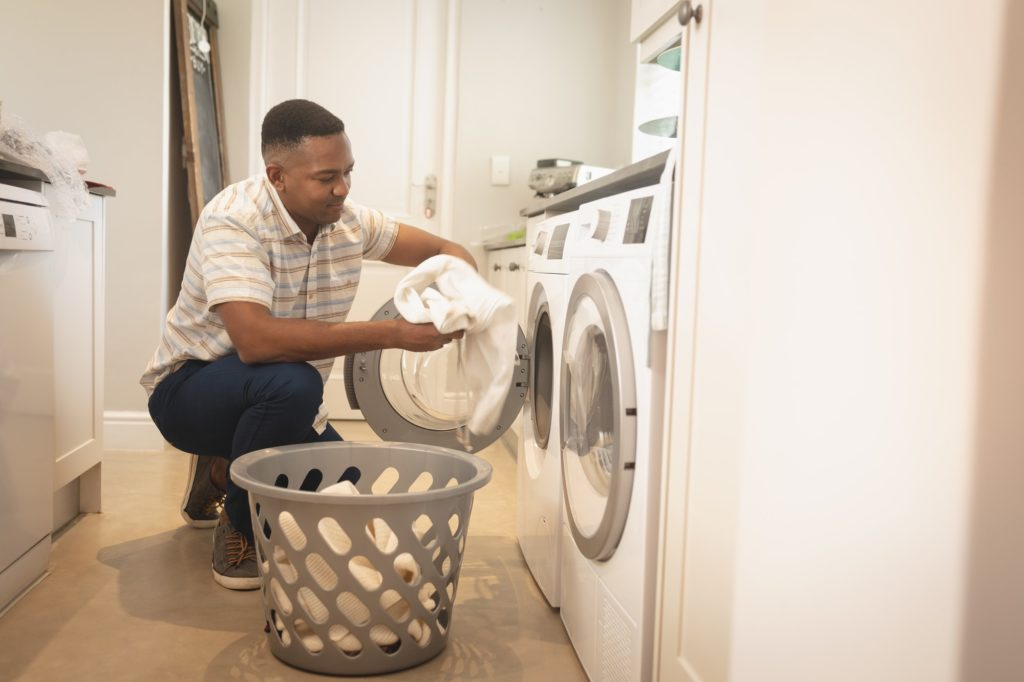 Side view of African American man washing clothes in washing machine at home